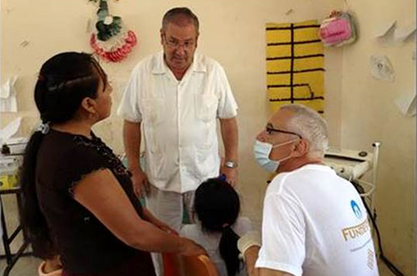 El padre Higinio Izquierdo, L.C. ayudando como traductor en una atención médica.