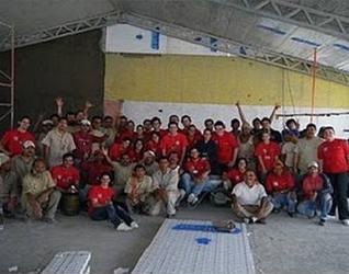 Miembros del Movimiento junto con reclusos construyendo una capilla.
