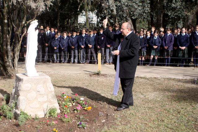 Mons. Mario Cargnello bendice la imagen de la Santísima Virgen que está a la entrada del colegio.