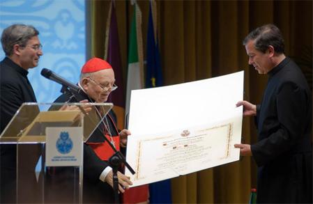 El Card. Elio Sgreccia recibe del P.  Álvaro Corcuera, L.C., el pergamino con el doctorado. A la izquierda aparece el padre Pedro Barrajón, L.C., rector del Ateneo Pontificio Regina Apostolorum.