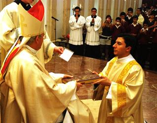 Mons. Pedro Pablo Elizondo, L.C. entrega los Evangelios al P. Santiago Garza, L.C, durante la ceremonia de ordenación.