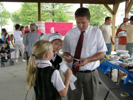 3rd grader Katie Brown (Mason) sells cheesecake raffle tickets to 5th grade teacher Matt Schlotman (Mason) as 5th grader Bradley Wier (Mason) looks on.