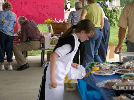 5th grader Katie Hart (Springboro) checks inventory levels while shoppers buy at other booths.