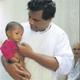El Padre Ravindra, mano derecha de la Madre Teresa, con un niño, en el dispensario médico.