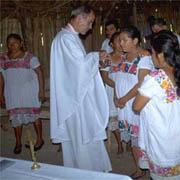 Sacerdote dando Comunión a mujeres indígenas.