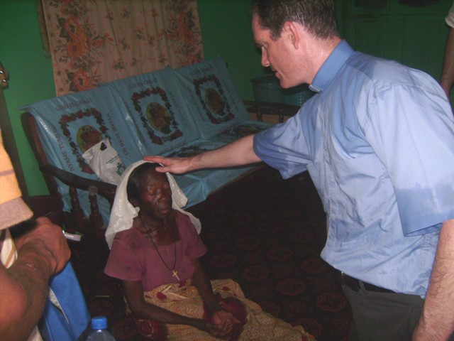 Fr Jeffery Jambon blessing Ghanian lady