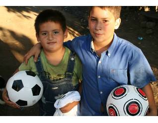 Two young boys make friends with soccer, a universal language.