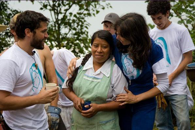 Eduardo Verástegui and missionaries gather around a local woman from Jonotla.