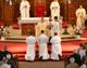 The three deacons kneel before the altar during the ceremony.