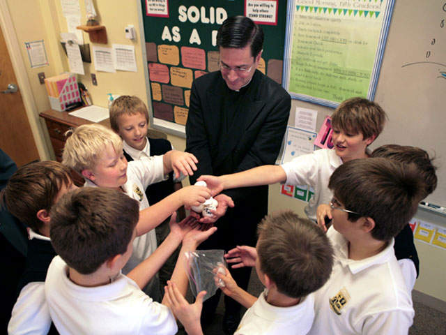 Fr. Timothy Mulcahey LC checks the �souls� of fifth graders (clockwise from Father) William O�Brien, Nicholas Alves, Luke Bick, Hugh Cole, Garrett Martin, Danny DeSimon, John O�Brien, and John Esswein.