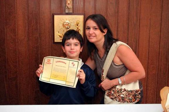 Un alumno, acompañado por su mamá, muestra su diploma que lo acredita como �Caballero del altar�.