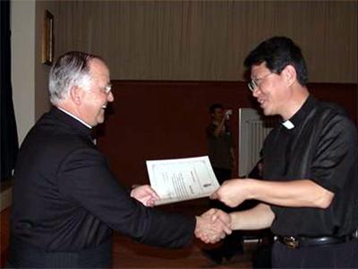 El P. Francisco Mateos, L.C., entrega el diploma de participación a un sacerdote coreano.