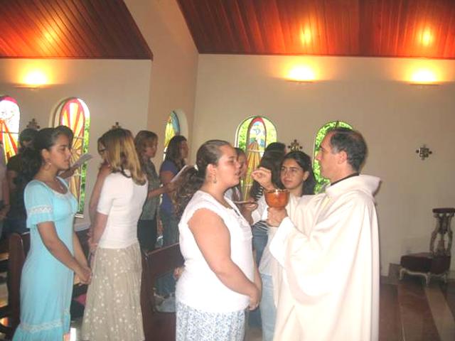 El P. Manuel Aromir, L.C., director territorial de Brasil, da la comunión a las participantes al curso para formadoras de Sudamérica.