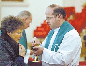 The Rev. Nikola Derpich, ordained in 2006 as a Catholic priest at the Vatican, administers communion to Gerrie Ridgeway during Mass Tuesday at Our Lady Help of Christians Church in Watsonville
