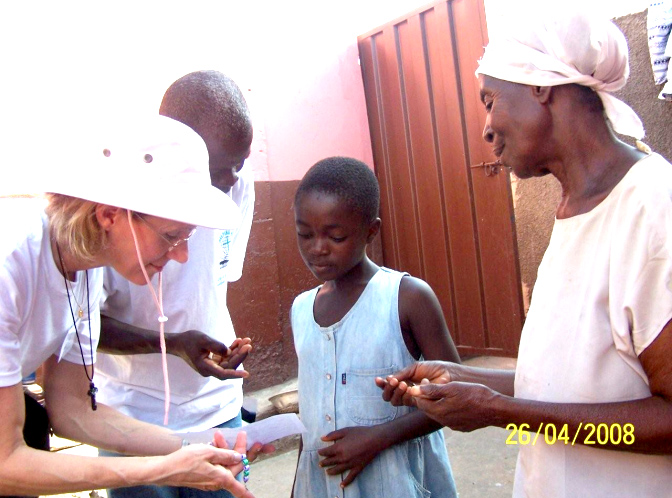 Julie Clements teaching children how to pray the rosary during a door-to-door visit.