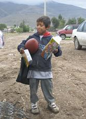 A child receives toys and food in the latest Hombre Nuevo mission in Baja California.