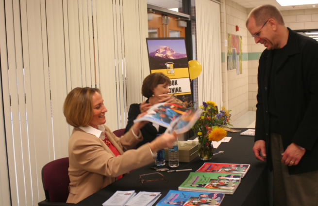 Dr. Coleen Kelly Mast gives some of her educational materials to David Olejnik of Shelby Township, Michigan, who came to hear her speak at the school open house for Everest on Nov. 9, 2008.