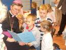 El obispo auxiliar de Colonia, Mons. Rainer Woeki, recibe los regalos de los niños del kinder.