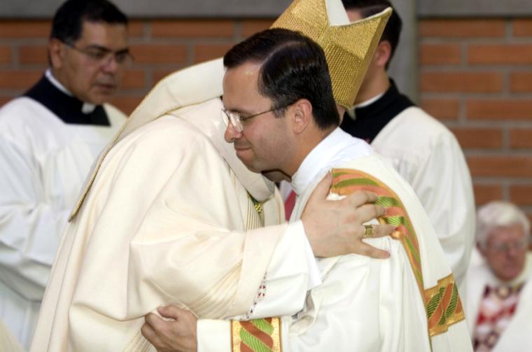 El P. Guillermo Herrera saluda al obispo después de su ordenación como diácono.