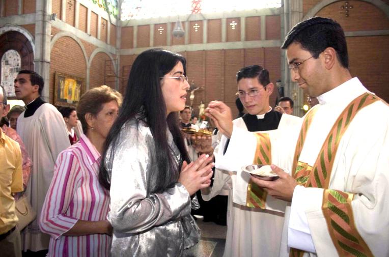El P. John Jader Vanegas da por primera vez la comunión a su hermana.