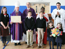 Bishop Malooly recieves gifts from Woodmont students. Father Steven Reilly, L.C. and Brother Ugo Piasentin, L.C. help to present the gift.