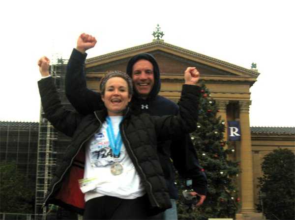 Geri and her husband doing the Rocky Balboa victory pose after the race