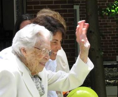 Mrs. Mee, desde su ventana, saluda a las consagradas el día de su último cumpleaños.