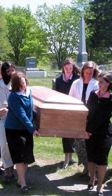 Señoritas consagradas llevan el féretro con los restos mortales de Mrs. Mee.