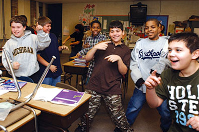 Students Dominic Goga, 11, far right, helps lead his class in a dance to motivate their brains in Julia Carlesso's math class at Wolfe Middle School in Center Line Public Schools.<i>Photo by David Schreiber</i>