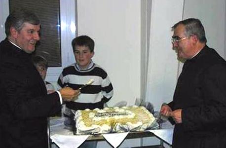 El P. Arrieta y el P. Fidel partiendo el pastel. En la cubierta se leía «Benvenuto, P. Giovanni!» (�¡Bienvenido, P. Juan!�).