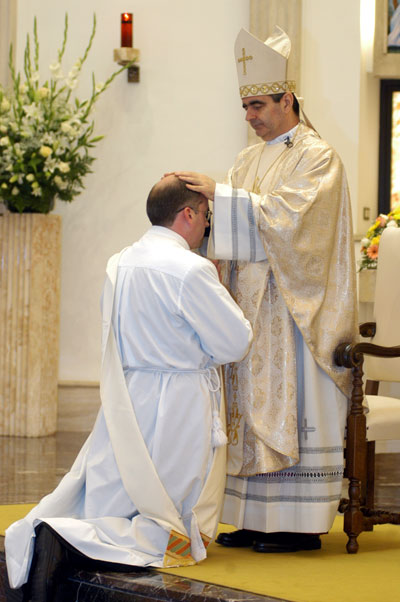 Archbishop Eterovic lays his hands on Nikola Derpich
