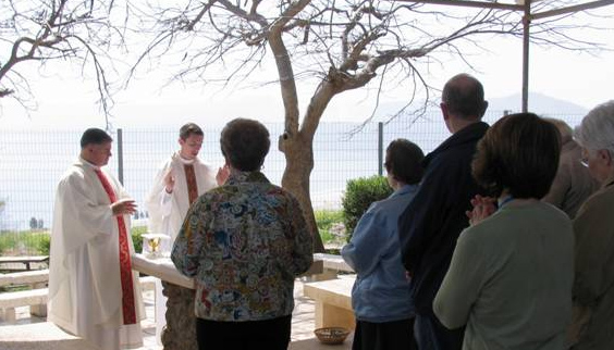 Mass at the Mount of the Beatitudes with the Sea of Galilee in the background and birds filling the air with their songs.