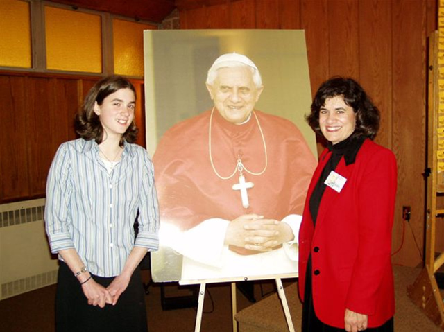 Mary Angela and her mother Carol Fisher, flanking a poster of Pope Benedict XVI.