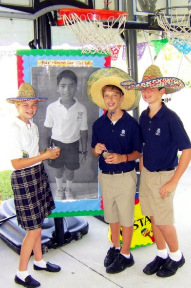 Three 8th grade students pose with a picture of Luis.