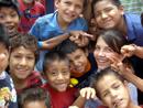 Carolina rodeada de niños a quienes les llevó un mensaje de esperanza y caridad.