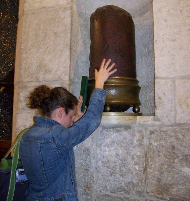 In the Church of the Holy Sepulcher, touching a piece of the pillar on which Jesus was scourged.