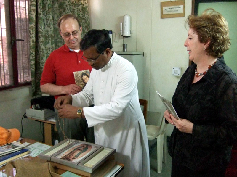 Marilupe y su esposo entregan al párroco de la Iglesia del Sagrado Corazón, en la India, unos retablos de la Virgen Peregrina de la Familia.