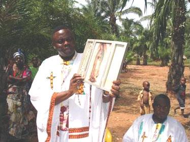 El P. Apolinar, sacerdote diocesano del Congo, África, con el retablo de la Virgen Peregrina de la Familia.